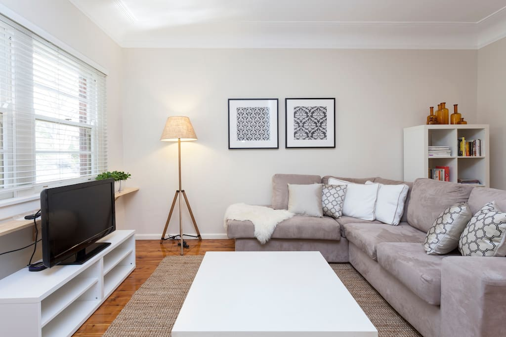 Spacious living room with stylish contemporary furnishings and a bright leafy outlook.