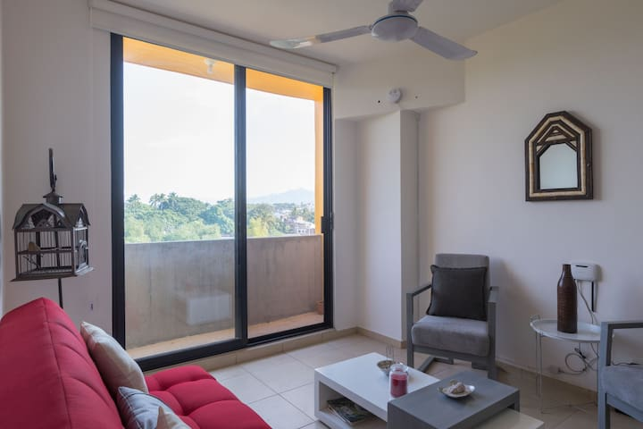 Sala con sofá cama smart tv con conexión a internet, balcón con vista panoramica al pueblo.