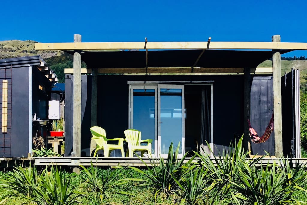 The front of the shipping container cabin, bifolding doors, deck, hammock, bathroom to the left.