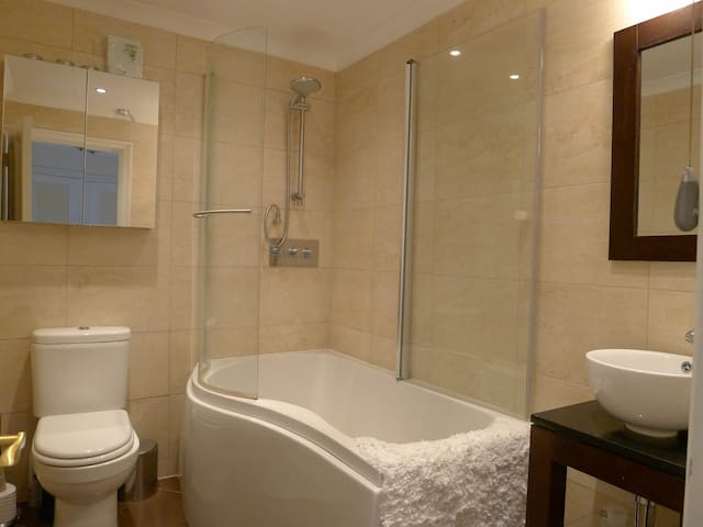 Modern bathroom with full bath and shower - relax after a long day.
