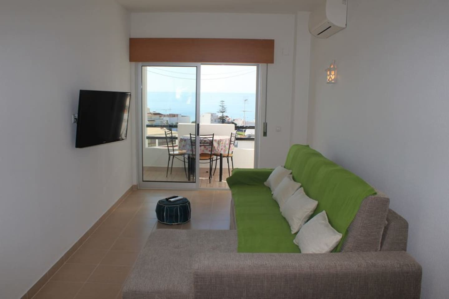 Living room with couch bed, TV, air conditioning, balcony and sea view