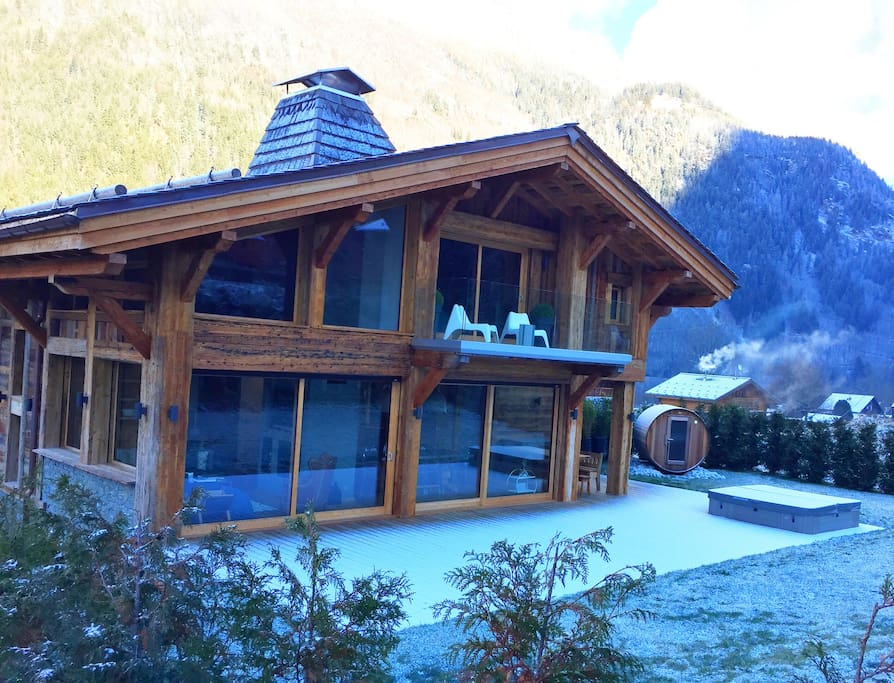 Luxury chalet with sliding glass doors leading onto the terrace with inset jacuzzi spa hot tub plus sauna