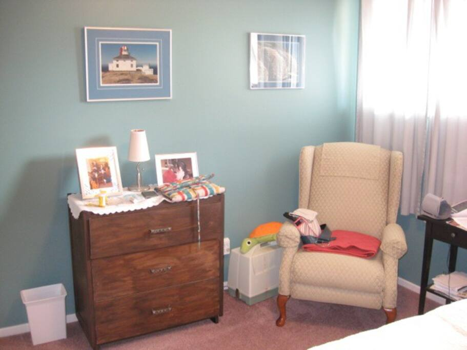 Comfy chair, side table, dresser, small lamp.