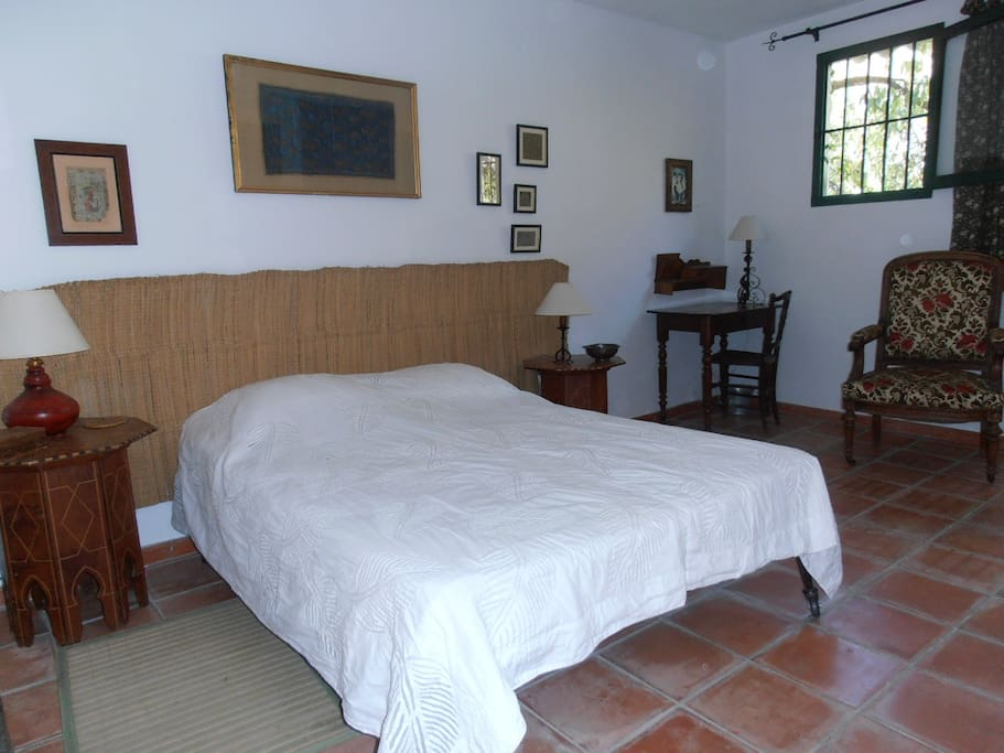 Room with double bed, with view of the swimming pool and the mountains.