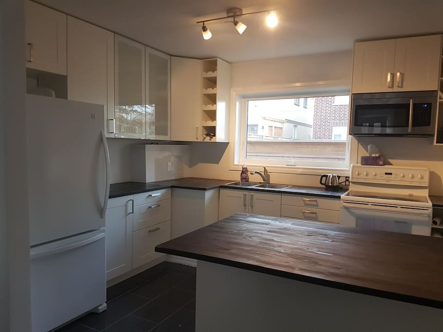 Newly-renovated large kitchen with cooking utensils