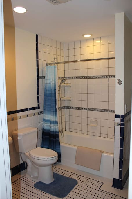 Private bath, turn of the century tile work and porcelain tub with shower.