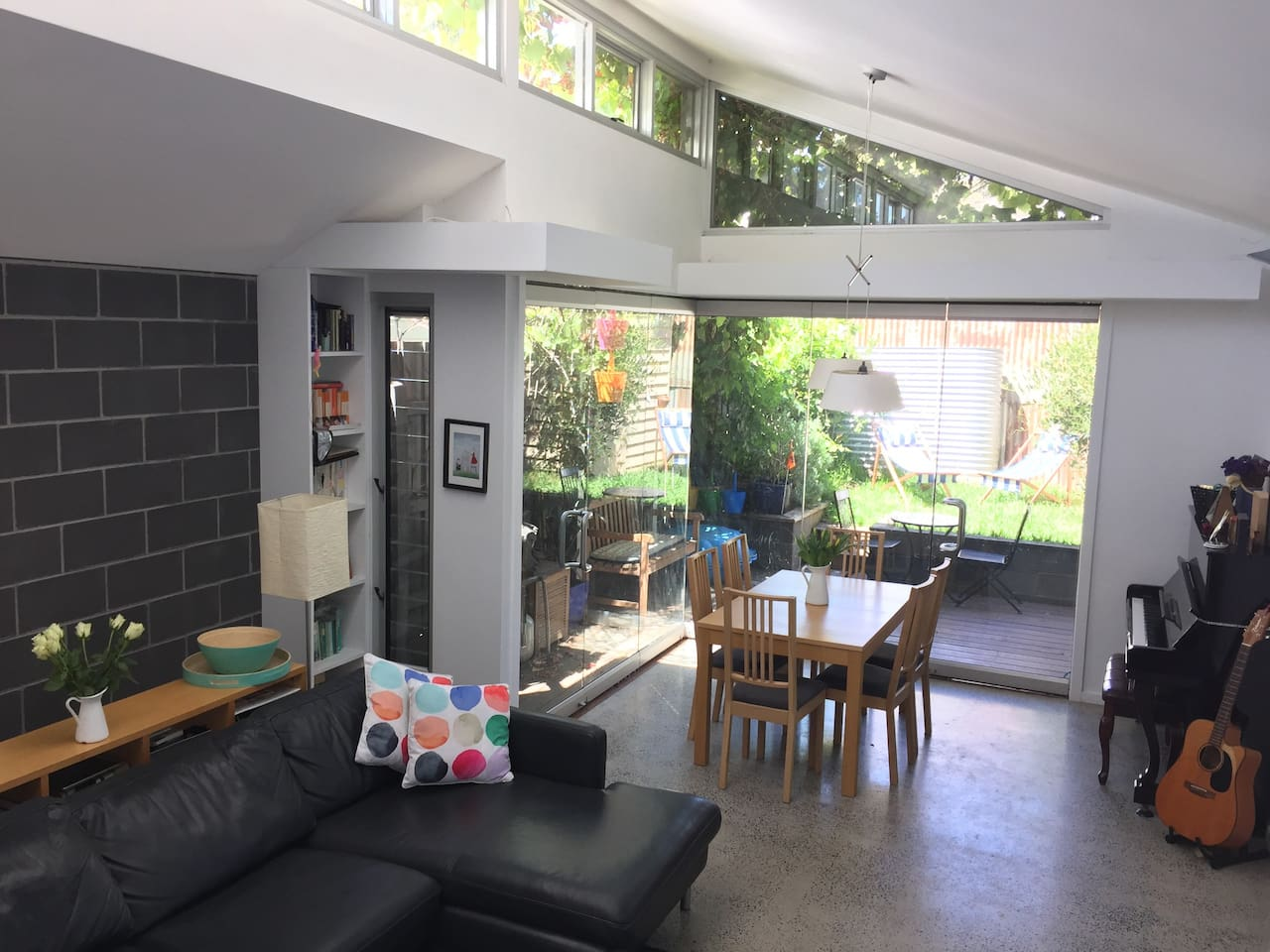 Sunfilled open plan living area with doors that completely open onto the deck.