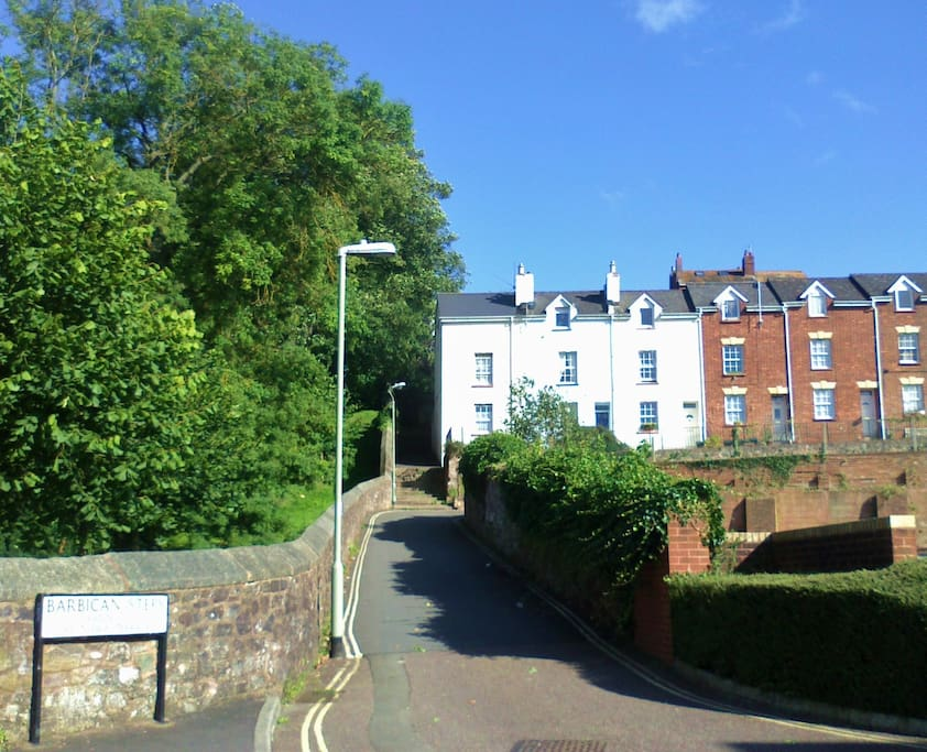 View of the house from Exe Street.  Walled road (leads to cul-de-sac). Steep steps between park and houses lead to city centre shops.