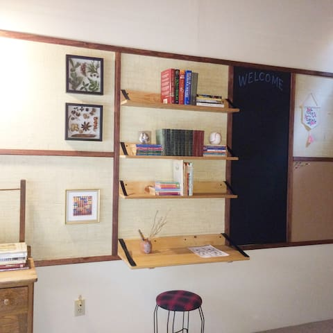 There is a small desk and stool with several wall mounted shelves above.  A blackboard and cork board finish the wall to the right.