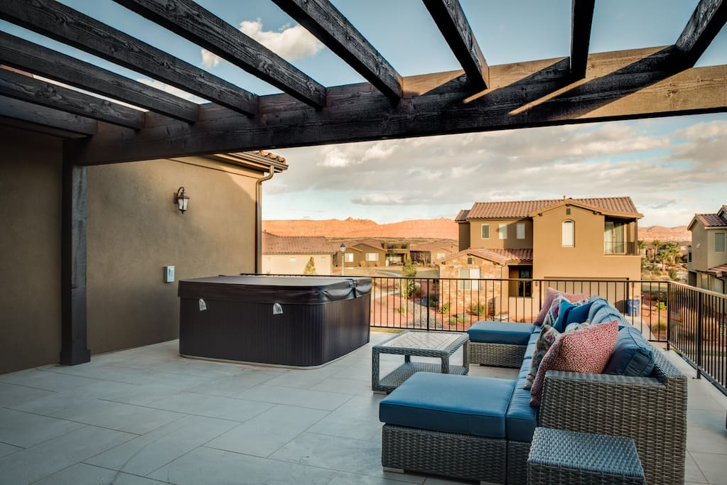 Upstairs patio with couches, hot tub, and an incredible view