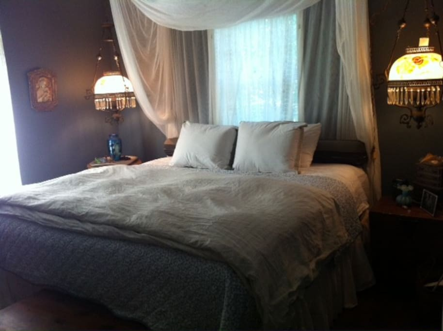 Giant king size bed with fine linens and vintage lighting.
