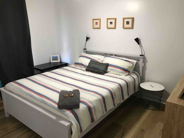 A second queen-sized bedroom with hotel quality bed linen, side tables, reading lamps and blockout curtains for a restful nights sleep. This bedroom has a ceiling fan.