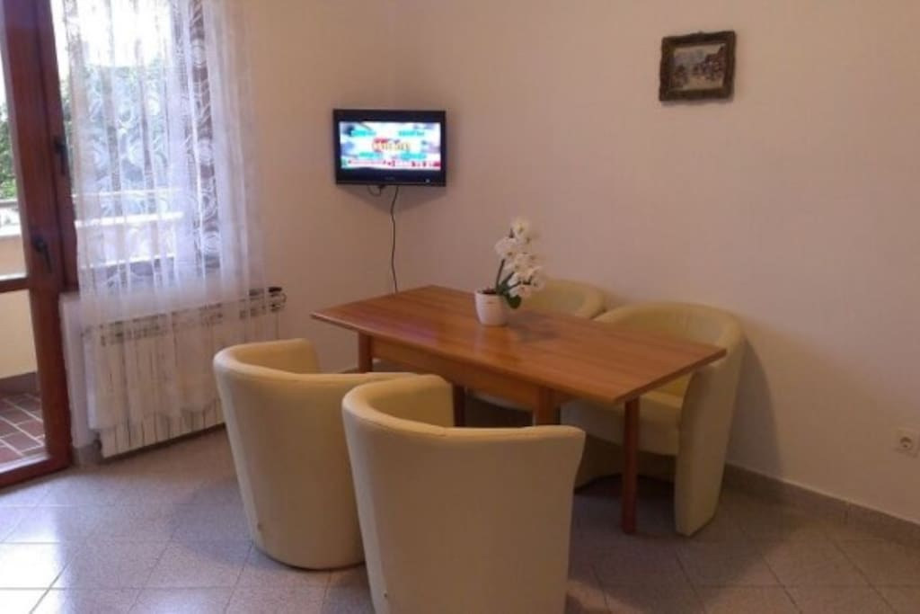 The livingroom with LCD TV, aircondition and kitchen.