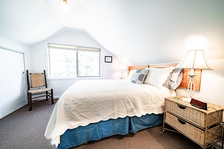 The second floor queen bedroom has a massive window at the same height as the forest canopy, giving you the feeling that you're up in a treehouse.