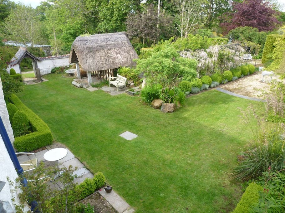 The garden in front of the cottage features a very ancient thatched well