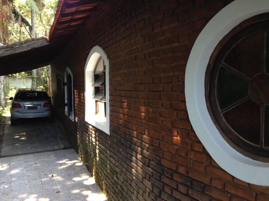 Vista lateral da garagem com vaga coberta para dois veículos e mais dois sem cobertura