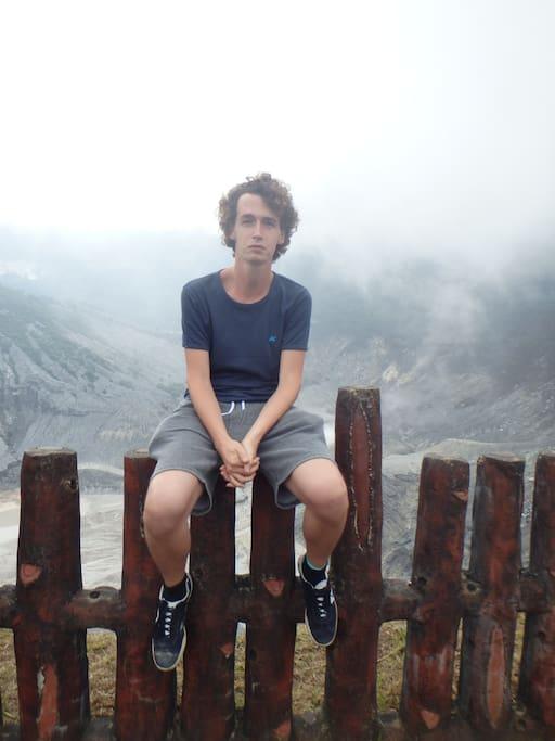 Ik op een hekje voor een mistige vulkaan in Indische.