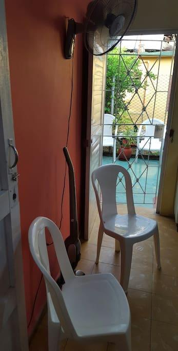 la habitacion vista desde otro angulo se muestra un ventilador y dos cillas.
