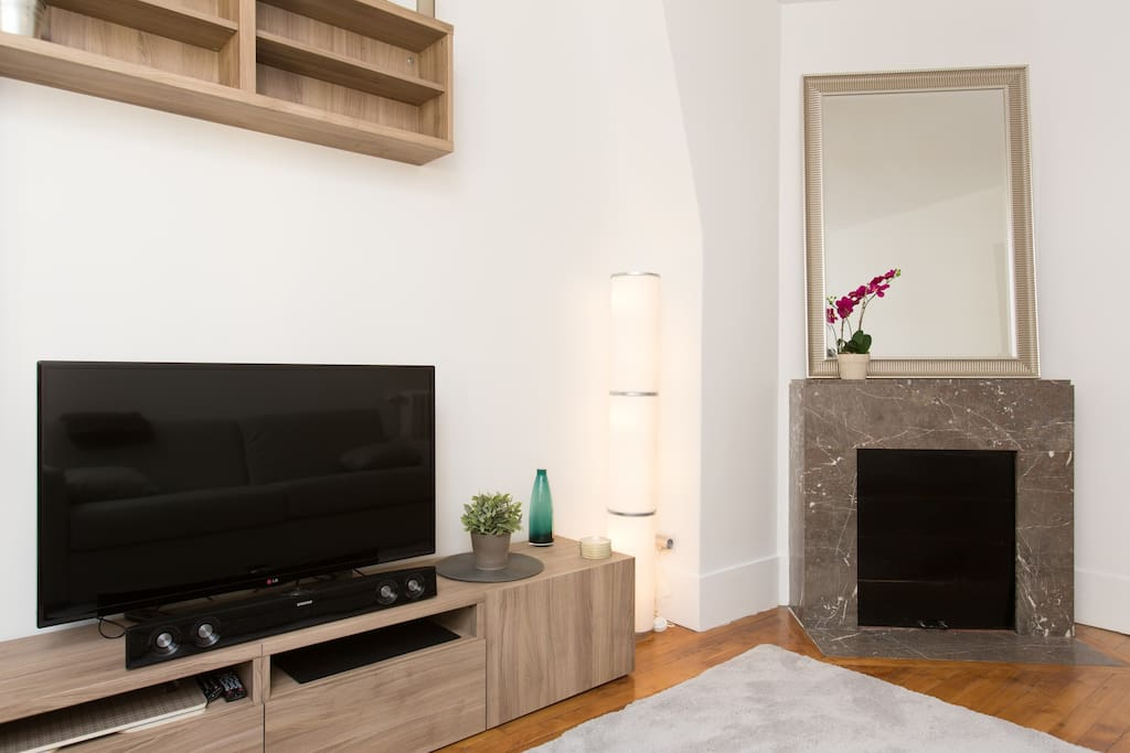 Big HD TV Screen, marble fireplace.