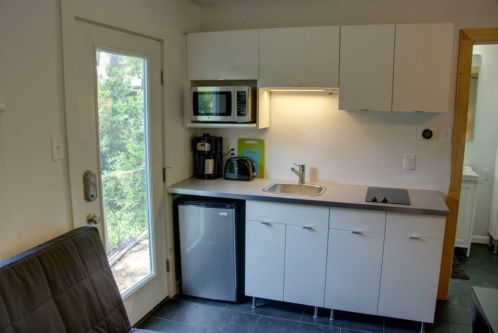 Kitchenette includes fridge, microwave, cooktop and sink.