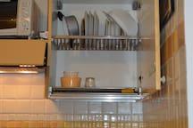 Cucina e armadietto per apppoggiare piatti. E' visibile il forno.