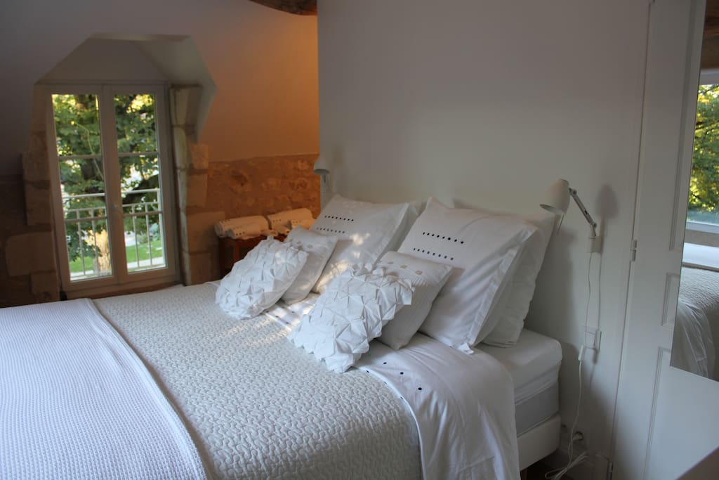 The ensuite bedroom with it's large window overlooking the stream