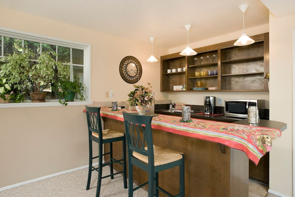 Your private kitchen and dining area complete with refrigerator,  coffee maker, microwave, sink, dishes, glasses, utensils, snacks, coffee, tea, juice, and cold bottled water.