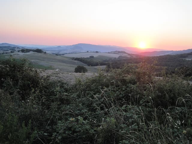 Sunset in the Tuscan hills. Podere Grignano is situated on top of the small hill with trees just left from the sun