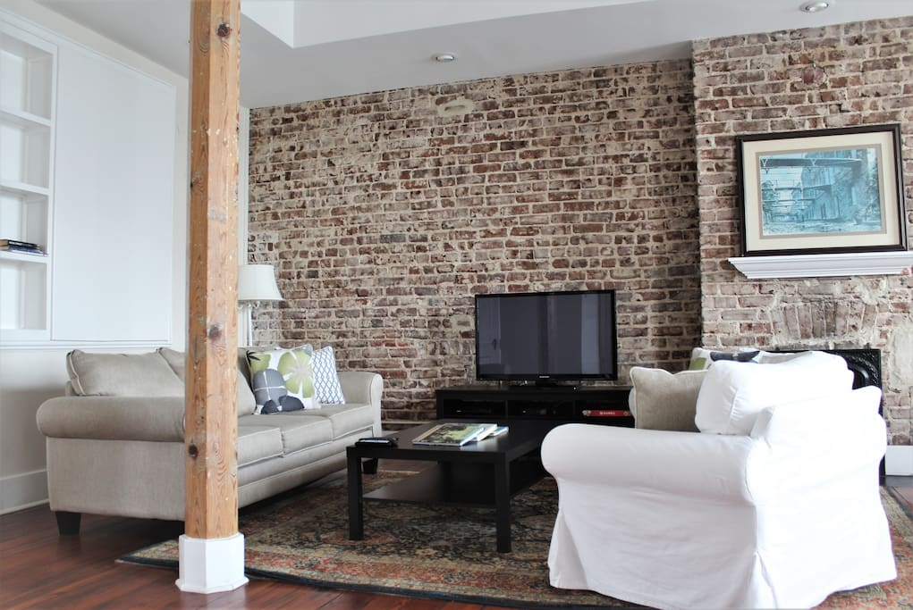 Souring ceilings, original Savannah gray brick walls, and picture windows make the open living and dining area the perfect spot to rest after a long day filled with exploring!