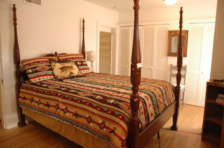 Queen bed in Bedrm. with en-suite 3/4 bathroom with slide panels closed.
