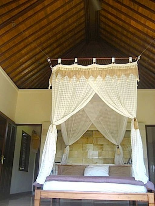 High vaulted ceilings and mosquito net in upstairs bedroom with rice field views.