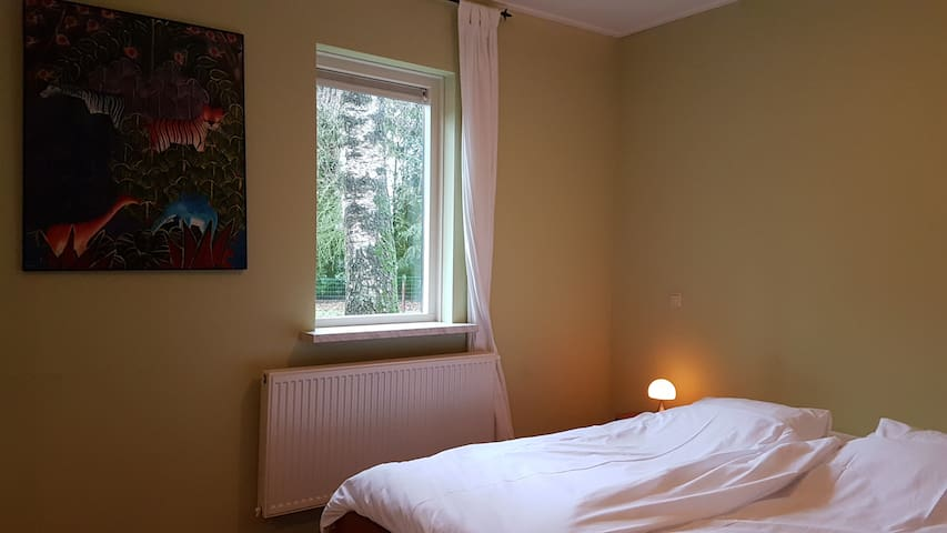 Gastenverblijf slaapkamer 3 met terrasdeuren naar berkenterras