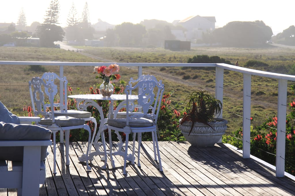 View from the patio over  the Conservation Greenbelt. 100 steps onto Longbeach, surfers, kite boards, horse riding - paradise.  Walk through the daisies to village shops and restaurants. End your day watching the sunset, sipping a glass of wine from our C
