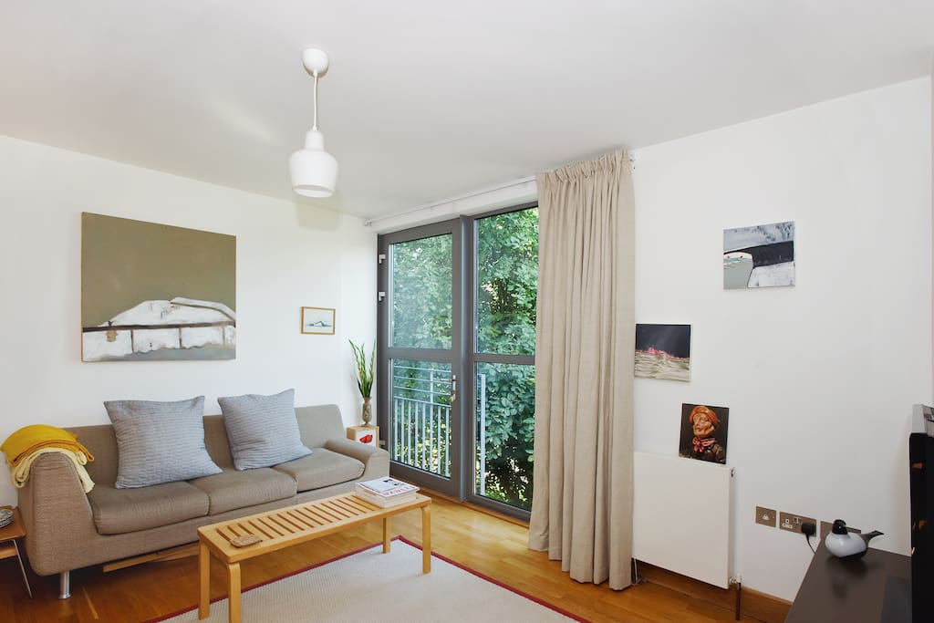 Cosy woolen rug and calm living space with full height windows out on to the park.