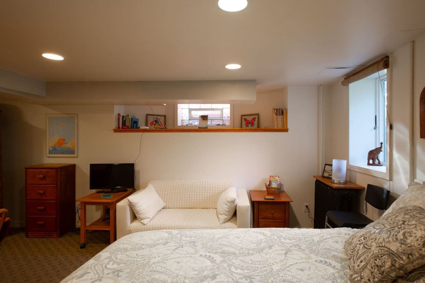Easement window. Sweet little couch.   Small TV and a dresser.