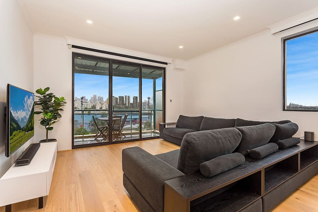 "Lounge Room - large 6 seater lounge - 60"" UHD smart TV - Foxtel - Expansive City & Harbour Views - Sonos Playbar x2 Play1 Speakers for surround sound."