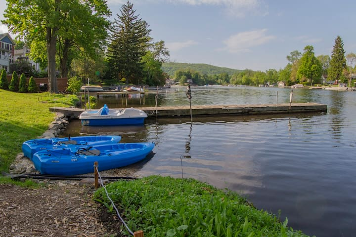 Waterfront area with pebble beach, kayaks, and paddle boat.