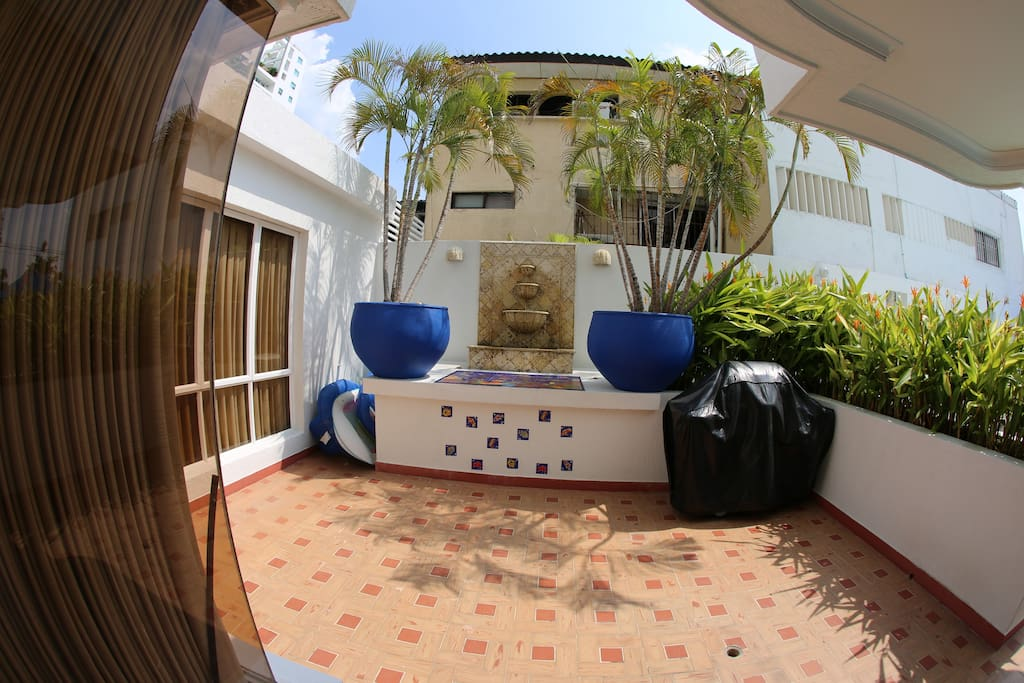 Our front patio with coral stone water fountain and bar-b-q. Steps to pool and best beach in Cartagena.