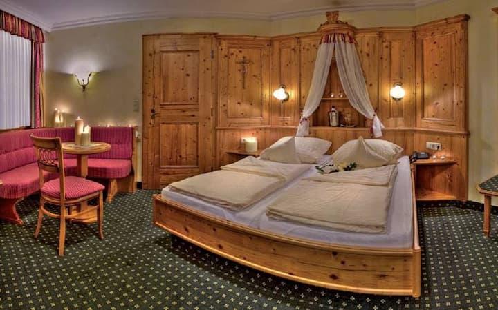 Natur- Wohlfühlhotel Brunner Hof OHG (Arnschwang), Romantik-Naturzimmer Melisse (ca. 27,5qm) mit gemütlicher Sitzecke mit Kachelofen