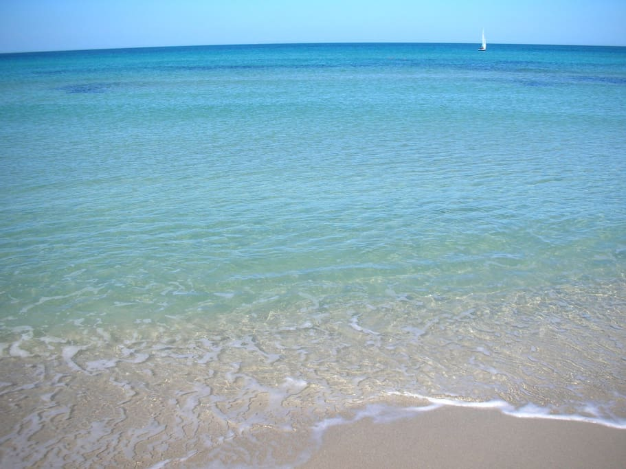 Sandy beach, low clean water, beautiful colors.