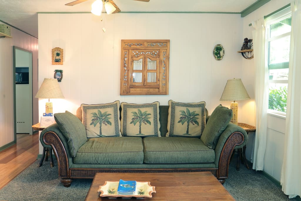 Living room with oversized couch with tropical theme