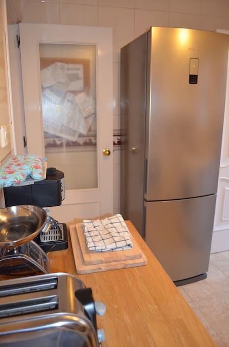 Kitchen appliances and fridge. Kitchen leads onto back patio