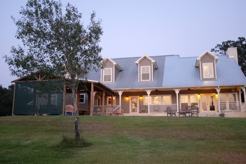 View of the back from the lake. A perfect porch for rocking chairs and a huge covered grilling area.