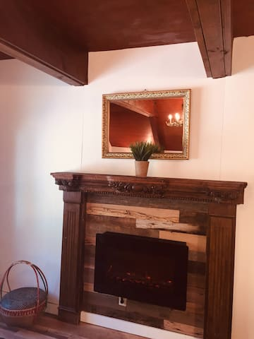 Electric fireplace across from queen bed for warmth and ambiance
