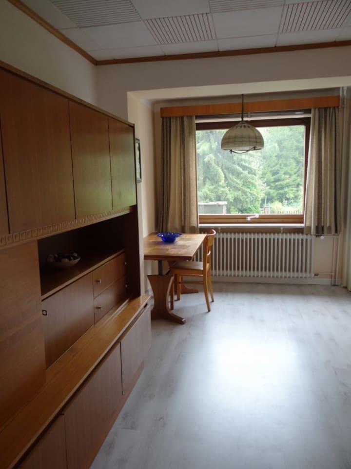 Wohnzimmer mit Schrankwand und Essbereich mit schönem Blick in den Garten