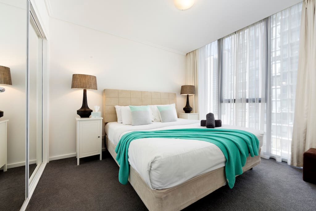 Spacious king bedroom very comfortable, pillow-top king bed, with large robe, spare towels, free Wi-Fi, city and bay views in this StayCentral Bayviews serviced apartment