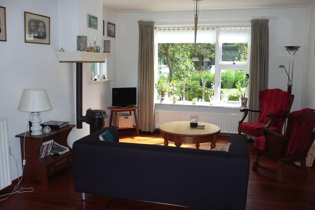 ruime woonkamer met gezellige houtkachel