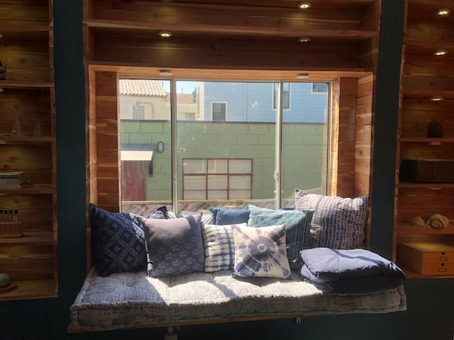 Prime view of the custom built cedar daybed with indigo Shibori mattress and pillows. View out the window is our urban farm sideyard with veggies and flowers.