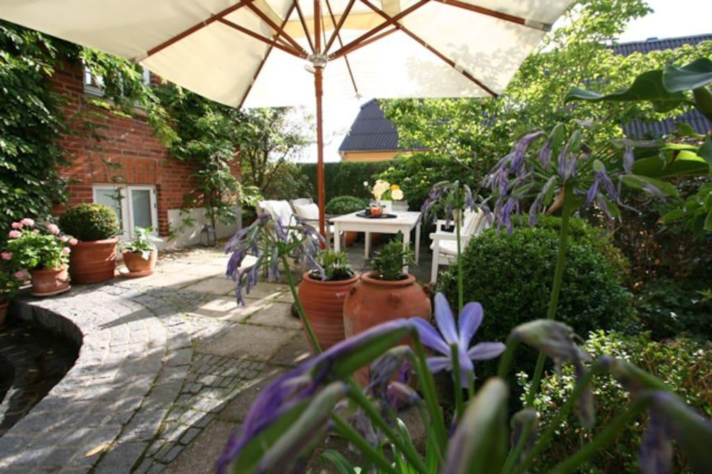 Hyggelig gårdhave med grill og gode havemøbler.