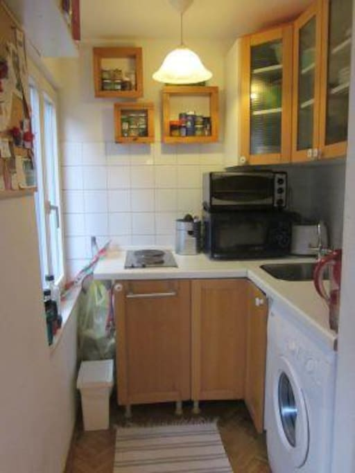 The kitchen, with a microwave, refrigerator, electric stove, pots, pans, cookware, complete glassware and silverware.
